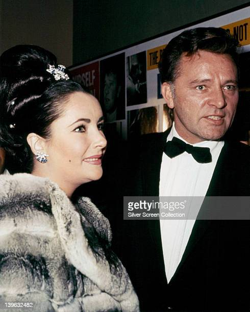 Elizabeth Taylor British actress wearing a grey fur coat and Richard Burton British actor wearing a black tuxedo with a white shirt and black bow tie...