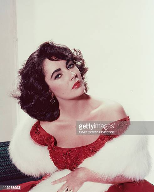 Elizabeth Taylor , British actress, wearing a red dress with a white fur stole in a studio portrait, against a white background, circa 1955.