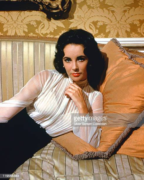 Elizabeth Taylor British actress wearing a sheer white blouse reclining against a cushion on a sofa in a studio portrait circa 1955