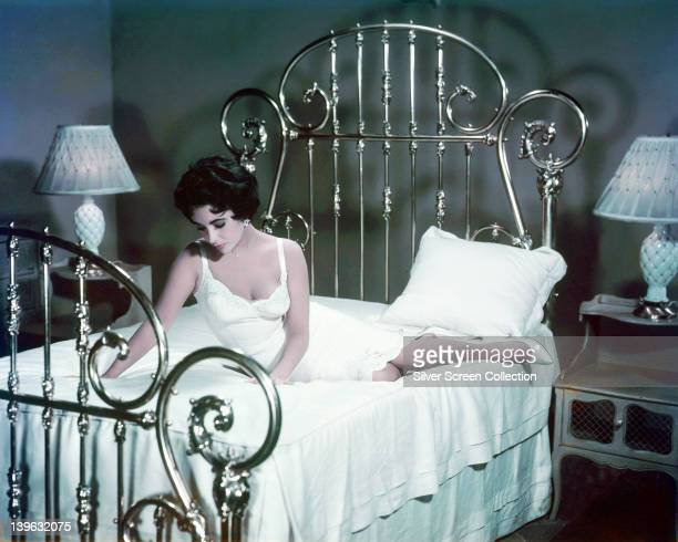 Elizabeth Taylor British actress wearing a white nightgown and sitting on a bed in a publicity still issued for the film 'Cat on a Hot Tin Roof' USA...