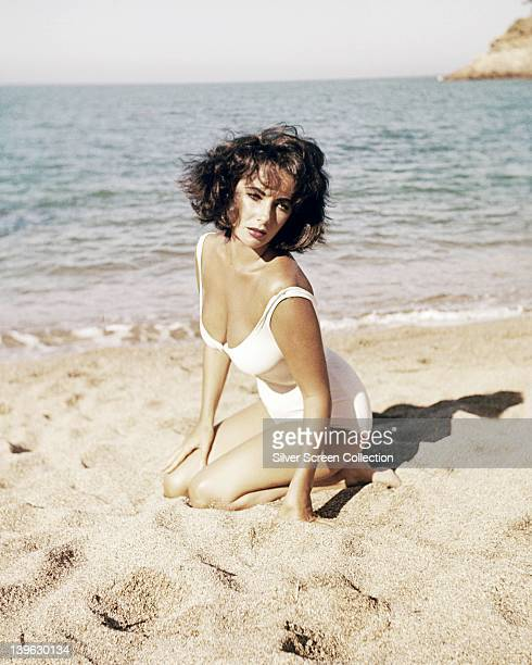 Elizabeth Taylor British actress wearing a white swimsuit as she kneels on the sands of a beach in a publicity still issued for the film 'Suddenly...