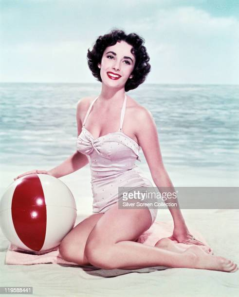 Elizabeth Taylor British actress wearing a white swimsuit sitting on a the sand with a beach ball in a studio portrait with the sea and horizon in...