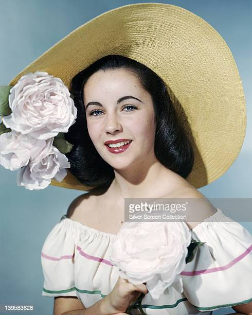 Elizabeth Taylor British actress wearing an offtheshoulder white dress with horizontal green and pink stripes and a widebrimmed straw hat with large...