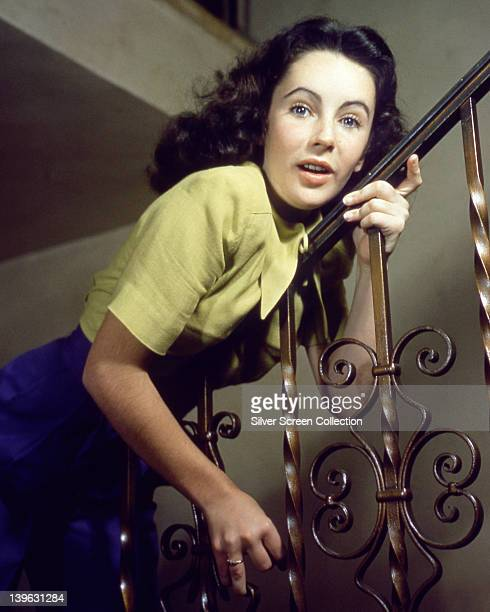 Elizabeth Taylor British actress wearing light green short sleeved top and a blue skirt leaning forward against the banister of a staircase circa 1955