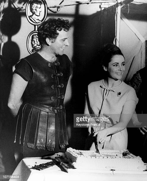Elizabeth Taylor cuts her birthday cake with the sword of Richard Burton who is in costume as Mark Antony for the film 'Cleopatra' on February 28...