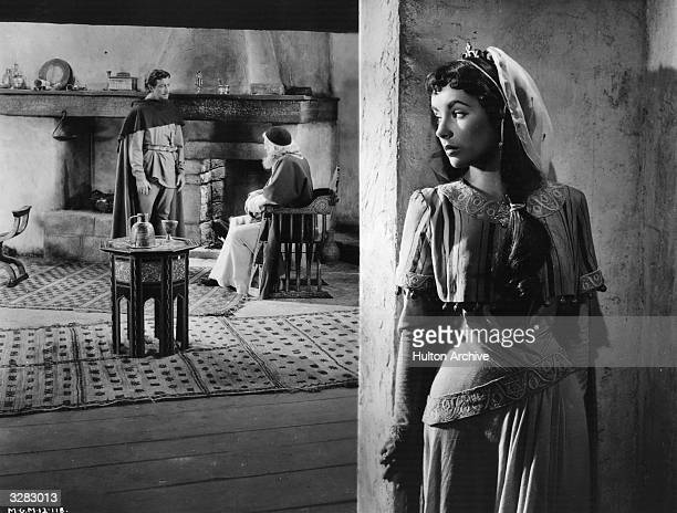 Elizabeth Taylor eavesdrops on a conversation conducted by Robert Taylor in a scene from 'Ivanhoe' based on the Sir Walter Scott novel of the same...