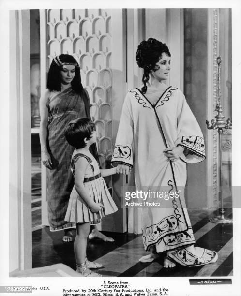 Elizabeth Taylor holding a child's hand in a scene from the film 'Cleopatra' 1963