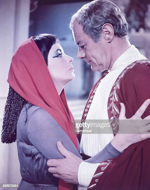 Elizabeth Taylor holds on to the arms of Julius Caesar played by Rex Harrison in the movie 'Cleopatra' 1963