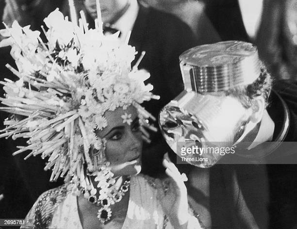 Elizabeth Taylor in a headdress of silver spikes, orchids and lilies chats to designer Pierre Cardin who is wearing what looks like an aluminium gas...