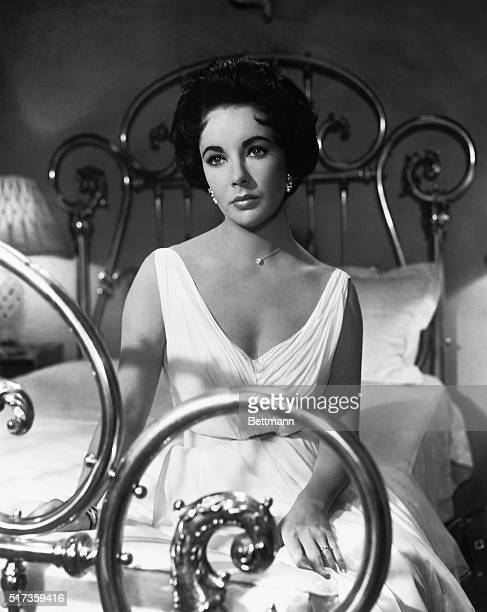 """Elizabeth Taylor in the 1958 MGM production, """"Cat on a Hot Tin Roof."""" She is shown wearing a white gown, seated on a brass bed."""