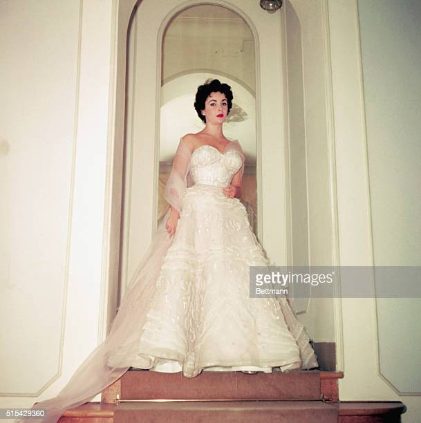 Elizabeth Taylor models for the Fontana Sisters here in Rome She is wearing a white full length gown