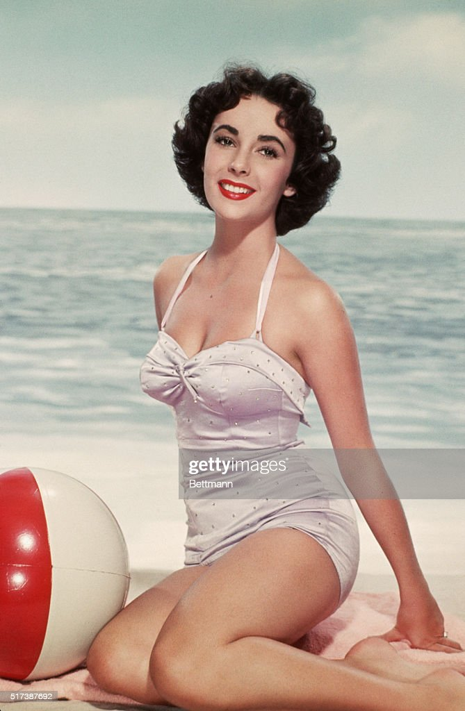 Elizabeth Taylor poses in a swimsuit with a beach ball.