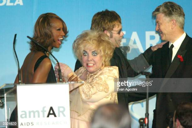 Elizabeth Taylor trying to steal Iman's diamond necklace at amfAr's Cinema against AIDS 2002 benefit gala at Le Moulin de Mougins during the 55th...