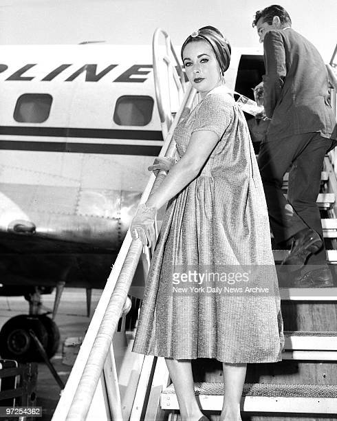 Elizabeth Taylor turns on unhappy expression as she boards plane at International Airport for Hollywood Earlier she heatedly denied any romance...