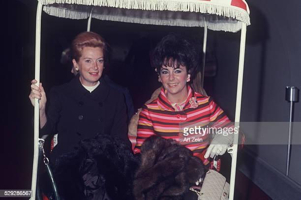 Elizabeth Taylor with Deborah Kerr in a golf cart; on vacation; circa 1970; New York.