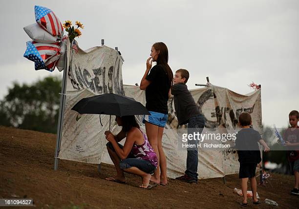 Elizabeth Turner of Littleton gets ready to write on a large canvas put up for thoughts and prayers at the makeshift memorial today July 27th 2012...