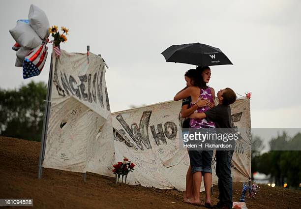 Elizabeth Turner of Littleton hugs her daughter Loryn 16 and son Logan 13 near a large canvas put up for thoughts and prayers at the makeshift...