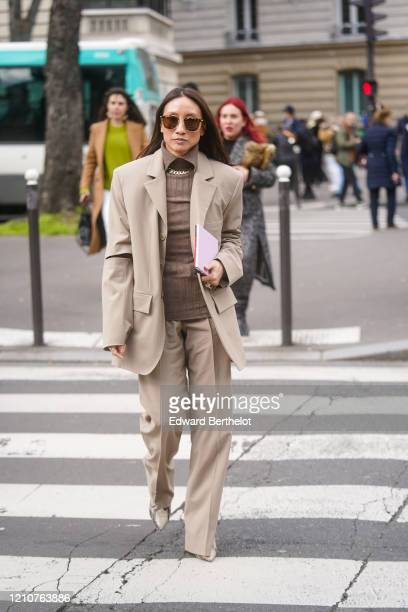Elizabeth Von Der Goltz wears sunglasses, a shirt, an oversized blazer jacket, flared pants, pointy shoes with snake pattern, outside Miu Miu, during...