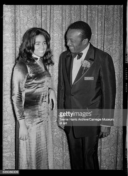 Elizabeth Young wearing velour dress and jazz musician Walt Harper wearing tuxedo with carnation on lapel standing in front of floral curtain...