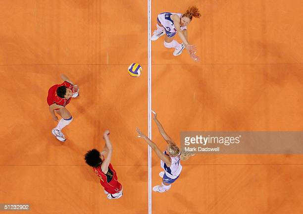 Elizaveta Tishchenko and Lioubov Shashkova of Russia go up to block a shot by Ping Zhang of China in the women's indoor Volleyball gold medal match...