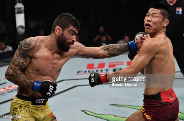 Elizeu dos Santos of Brazil punches Li Jingliang of China in their welterweight bout during the UFC Fight Night event at Shenzhen Universiade Sports...