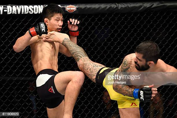 Elizeu Zaleski dos Santos of Brazil kicks Keita Nakamura of Japan in their welterweight bout during the UFC Fight Night event at the Moda Center on...