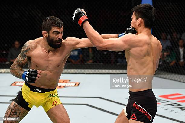 Elizeu Zaleski dos Santos of Brazil punches Keita Nakamura of Japan in their welterweight bout during the UFC Fight Night event at the Moda Center on...