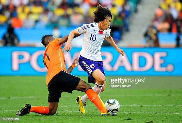 Eljero Elia of the Netherlands tackles Shunsuke Nakamura of Japan during the 2010 FIFA World Cup South Africa Group E match between Netherlands and...