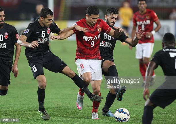 Elkeson De Oliveira Cardoso of Guangzhou Evergrande in action against Walid Abbas and Majed Hassan of Al Ahli during the Asian Champions League Final...