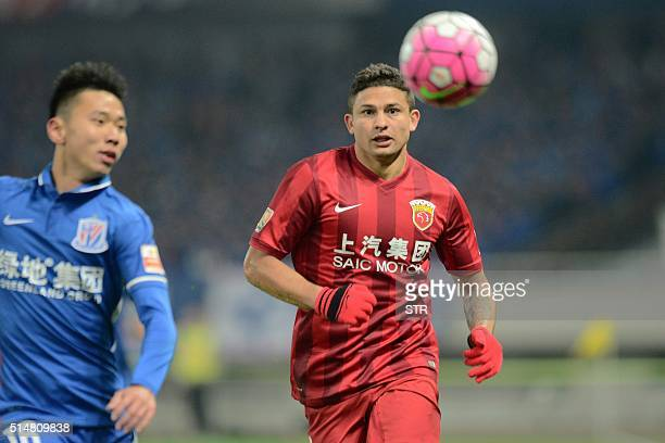 Elkeson De Oliveira Cardoso of Shanghai SIPG competes for the ball with Li Yunqiu of Shanghai Shenhua during their Chinese Super League football...