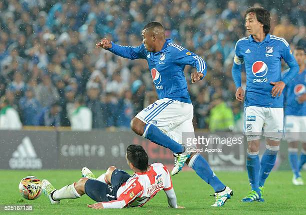 Elkin Blanco of Millonarios struggles for the ball with Juan Guillermo Dominguez of Junior during a match between Millonarios and Junior as part of...