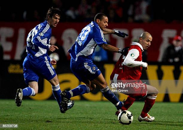 Elkin Soto of Mainz is challenged by Jermaine Jones and Mladen Krstajic of Schalke during the DFB Cup quarter final match between FSV Mainz 05 and FC...
