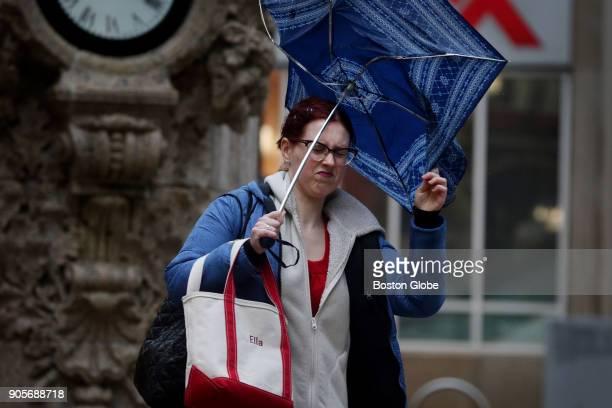 Ella Bessmer hangs onto her umbrella while walking amid rain and wind on Washington Street in Boston on Jan 12 2018
