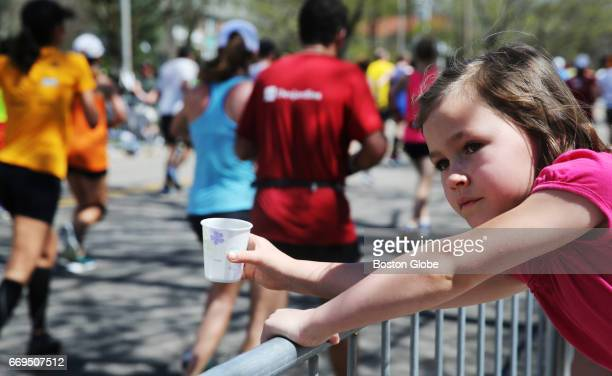 Ella Eaton offers water to runners climbing Heartbreak Hill on Commonwealth Avenue in Newton MA during the 121st running of the Boston Marathon on...