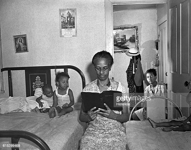Ella Watson a US government charwoman reading the bible to her adopted daughter and three grandchildren Washington DC August 1942