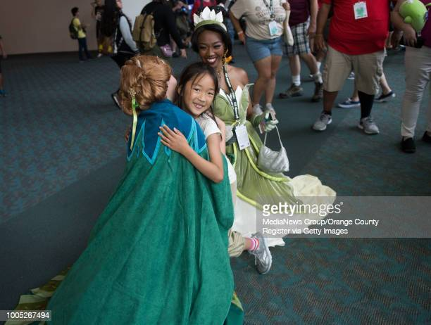 Ella Wong of San Francisco gets a hug from Hayley Smith dressed as Anna from 'Frozen' as Asia Smith dressed as Princess Tiana looks on during...