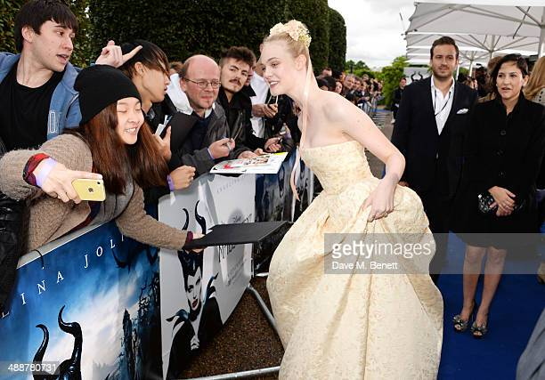 """Elle Fanning signs autographs at a private reception as costumes and props from Disney's """"Maleficent"""" are exhibited in support of Great Ormond Street..."""