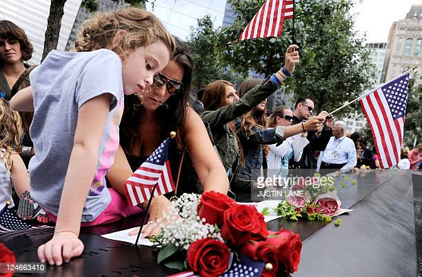 Elle Jackman helps her mother Iris Jackman do a rubbing of her aunt's name Brook Alexander Jackman at the North Pool of the 9/11 Memorial during...