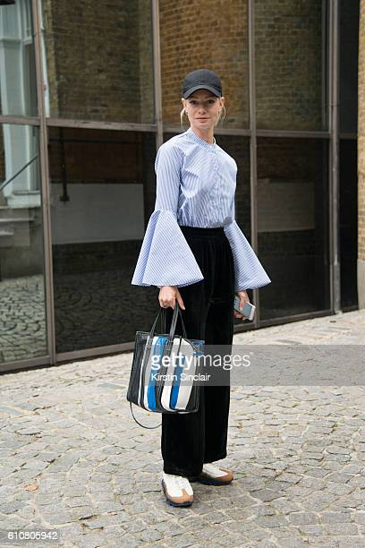 Elle Netherlands fashion editor and freelance stylist Lisa Anne Stuyfzand wears an Asos shirt Ganni trousers Celine bag Nike trainers and a vintage...