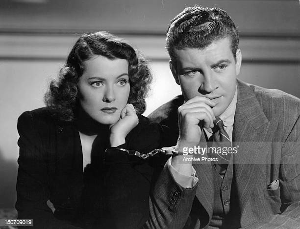 Ellen Drew and Robert Preston are handcuffed in a scene from the film 'Night Of January 16th' 1941