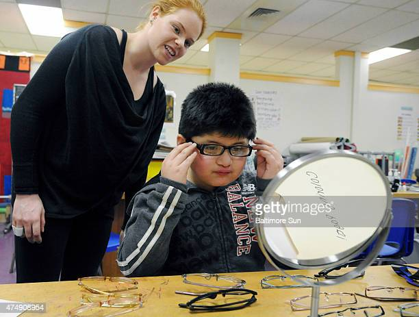 Ellen Marcus research assistant and a student at Johns Hopkins University secondgrader Anthony Martinez try on eyeglass frames Dr Megan Collins gave...