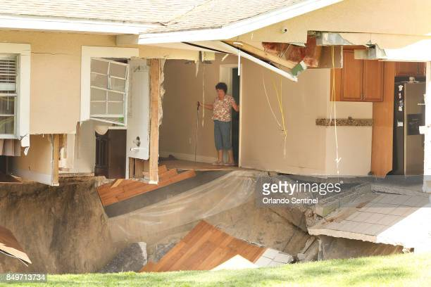Ellen Miller carefully surveys the damage as her home at 222 West Kelly Park Road in Apopka is being swallowed by a sinkhole on Tuesday Sept 19 2017...