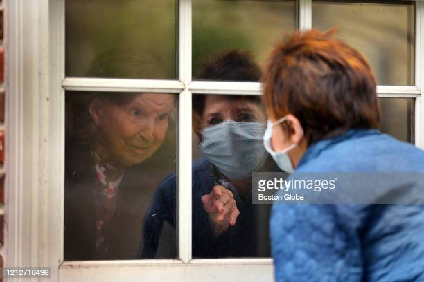 Ellen Taylor talks to her mother Eva Taylor age 100 through the first floor window in Jamaica Plain in Boston on May 8 2020 The Rogerson House...