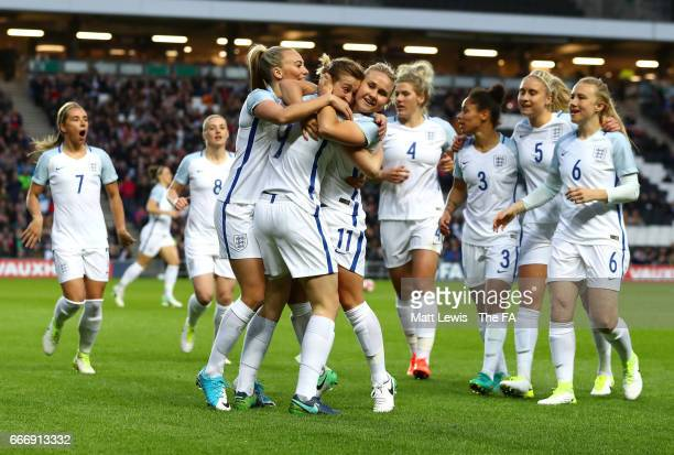 Ellen White of England celebrates with team mates as she scores their first goal during the Women's International Friendly match between England and...