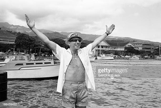 Elles Et Eux ' In Tahiti En 1961 'ELLES et EUX' à TAHITI Sur un port portrait de Charles TRENET chemise ouverte lunettes noires et chapeau lévant les...