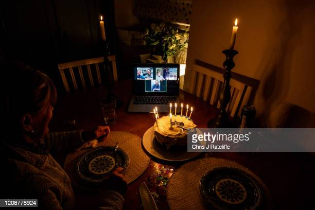 Elli Ratcliffe presents a birthday cake for her son Chris Ratcliffe on his 35th birthday in front of a Zoom video conference with his wife Jenny,...