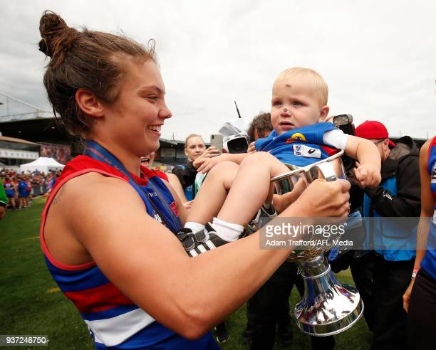 Ellie Blackburn of the Bulldogs puts her nephew into the premiership cup with Katie Brennan of the Bulldogs during the 2018 AFLW Grand Final match...