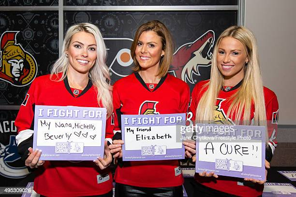 Ellie Campbell girlfriend of Marc Methot Liane Cote EJ Gallo Winery and Monika Caryk girlfriend of Mike Hoffman hold placards in support of Hockey...