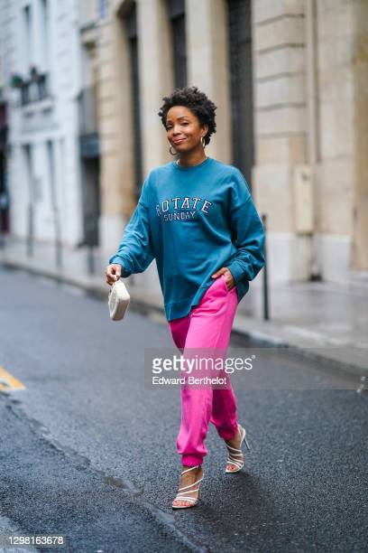 Ellie Delphine aka SlipIntoStyle wears earrings, a blue oversized wool pullover from Rotate, neon pink jogger sport pants from Rotate, a small white...