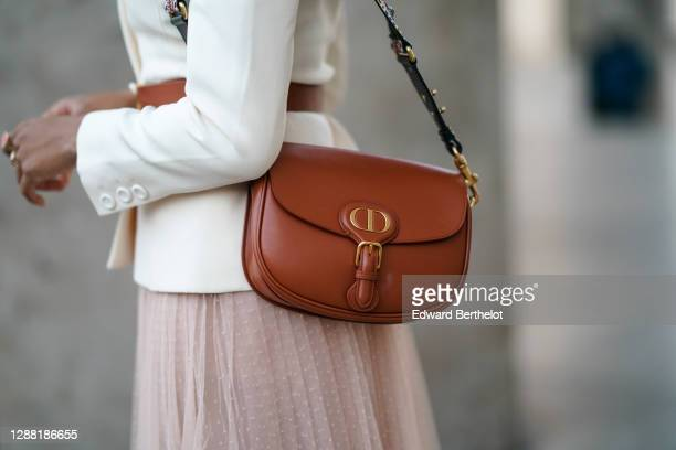 Ellie Delphine wears a brown leather Dior bag, on November 27, 2020 in Paris, France.